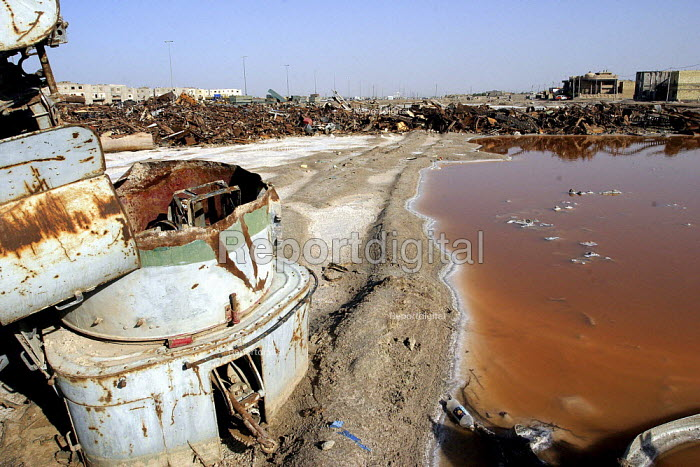 The wreckage of war - tank treads and turrets - in the middle of a residential neighborhood, the houses are in the background. The wreckage includes depleted uranium ammunition, a big health hazard to residents. - David Bacon - 2005-05-26
