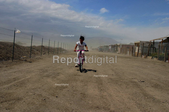 A young girl rides her bike through a sandstorm in Chicanitas, a farm labor camp of trailers in the desert in Coachella Valley. Many of the camps residents are Purepecha migrants from the Mexican state of Michoacan. California USA - David Bacon - 2006-04-13