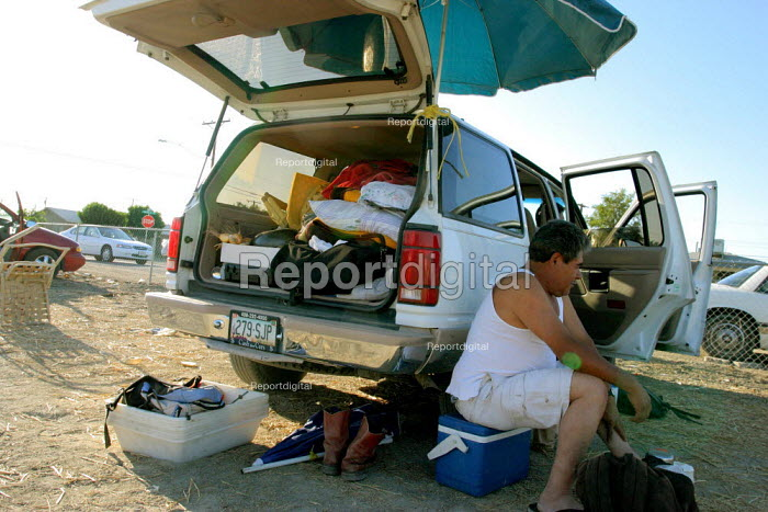 At the height of the grape harvest, many workers eat and sleep next to their cars in two parking lots in Mecca, a small farm worker town in the Coachella Valley. The growers and government authorities do not provide housing for seasonal grape pickers. California USA - David Bacon - 2006-05-30