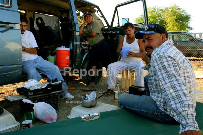 At the height of the grape harvest, many workers eat and sleep next to their cars in two parking lots in Mecca, a small farm worker town in the Coachella Valley. The growers and government authorities do not provide housing for seasonal grape pickers. From right, Enrique Saldivar, Leoncio Mendoza and Alfonso Leal come from Mexicali, on the US border 100 miles to the south, to pick grapes every year. California USA - David Bacon - 2006-05-30