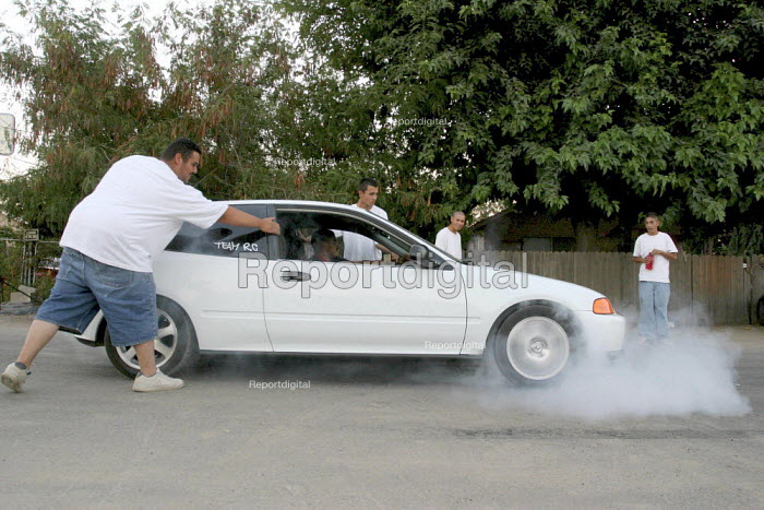 """Young farm workers in Raisin City have formed a car club, """"Team RC,"""" and show off their cars after work. California USA - David Bacon - 2006-09-05"""