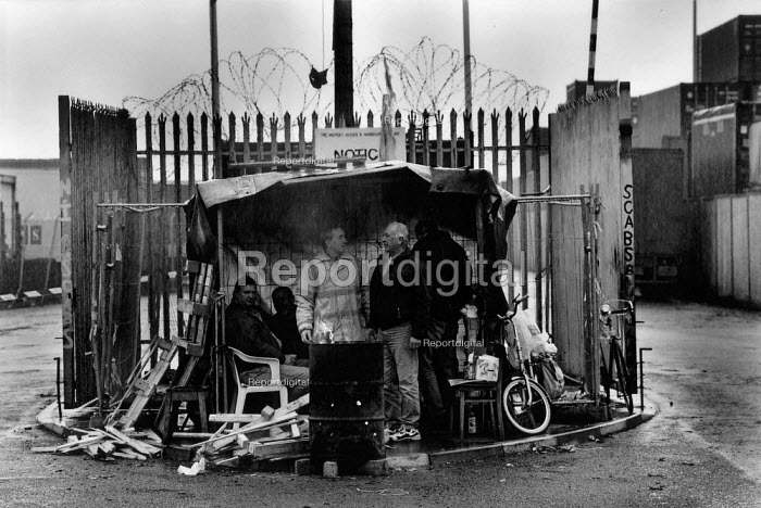 Pickets with their hut and brazier at the dock gates during the two and a half year long dock dispute during which 400 dockers were sacked for refusing to cross a picket line, during which time the strike remained unofficial (TGWU) and the picket secondary. Liverpool Docks - David Sinclair - 1997-09-12