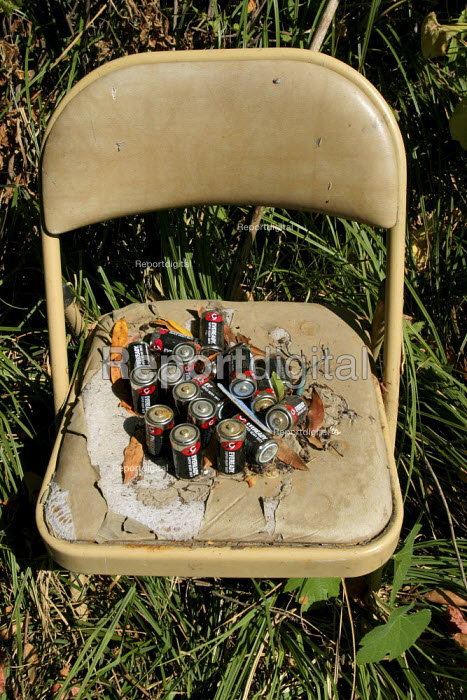 Exhausted batteries collected on a chair outside a shack built by Mexican migrant farm workers, Sonoma County. California USA - David Bacon - 2006-08-05