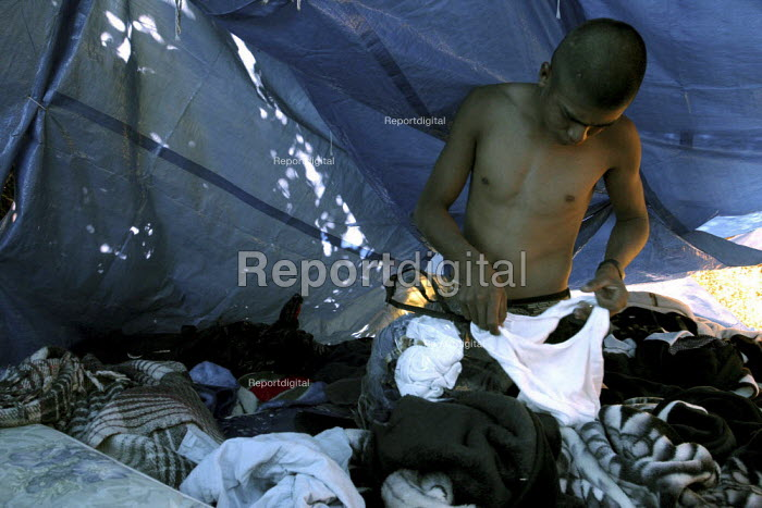 A young man gets dressed in his sleeping tent in a camp set up by migrant workers from the Mexican state of Oaxaca, who live in temporary shelters next to a field of wine grapes. The workers are Chatinos, and use their cultural practices and family ties to support each other while looking for farm work in Sonoma County, one of the wealthiest wine-producing areas of the US. - David Bacon - 2004-06-26