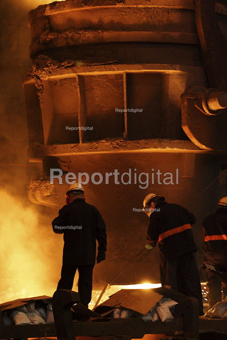 Steelworkers standing in front of a ladle containing 100 tons of molten metal on a pouring platform. Pouring molten metal into a cast from the furnace. Sheffield Forgemasters Steelworks. - David Chang - 2006-12-20
