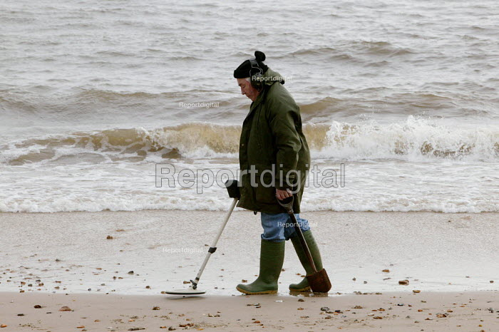 Retired elderly man, well wrapped up against the winter cold, is seen using his metal detector on the beach at Christchurch, near Bournemouth - David Mansell - 2004-12-25
