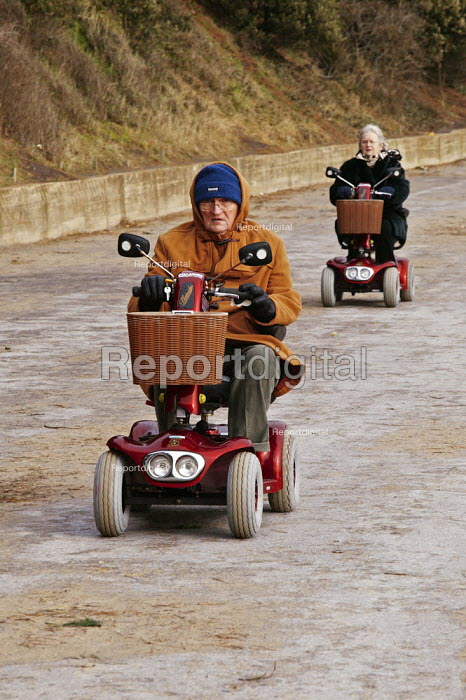 An elderly man is seen driving his motorized invalid scooter. - David Mansell - 2004-12-25