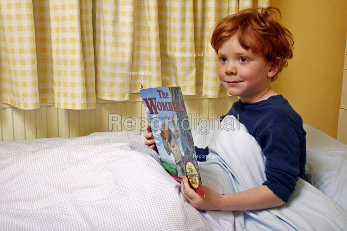 Bedtime reading. Five year old Jamie is seen reading one of his books in his bed before he goes to sleep. - David Mansell - 2004-06-22