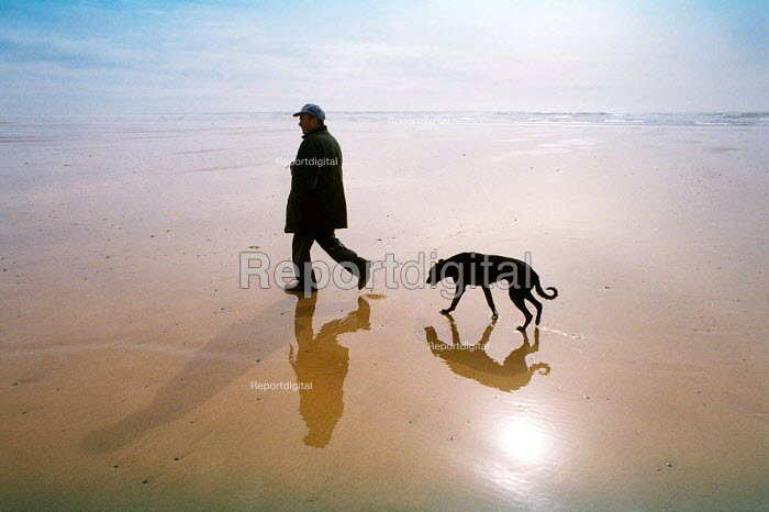 Beach walk feature for Travel. Freshwater Bay West in the Pembrokeshire national park, Wales. Man walking with his dog - David Mansell - 2001-03-31