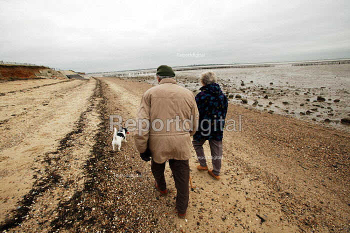 Retired old people seen walking with their dog along the beach at Cudmore Grove Country Park, East Mersea, Essex. - David Mansell - 2002-12-12
