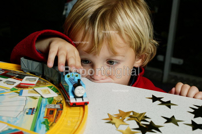 Thomas the Tank Engine, one of the best selling children's toys is being played with by 3 year old Johnnie Walkins, at Hamleys Store, London. - David Mansell - 2005-10-23