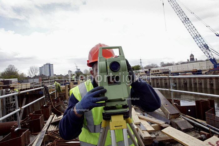 A surveyor seen using his theodolite at the construction and engineering work being undertaken by British Waterways to build a set of lock gates on the River Lee, which will enable heavy building materials to be carried by river transport into the site of the 2012 London Olympic Complex.building workers health and safety steel erection - David Mansell - 2008-04-07