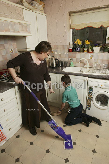 Maxine Steinberg whos a mother, housewife and has a part time job, is given some help by her young son to do some of the house work, seen sweeping up the kitchen floor. - David Mansell - 2008-04-09
