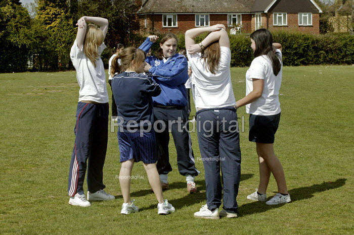 Cover Student Sarah Maeght a sixth form A level student who attends The Chalfonts Community College in Gerrards Cross, Buckinghamshire, and who is paid to help cover lessons when needed by the school. Sarah wants to become a PE teacher and is seen taking a rounders lesson, photograph shows girls stretching and warming up. - David Mansell - 2008-04-23