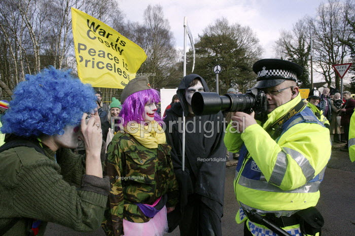 Anti-nuclear campaigners, dressed up as circus clowns tormenting a police officer who is using a camera to record the faces of people gathered outside the Atomic Weapons Establishment at Aldermaston, Berkshire. - David Mansell - 2008-03-24