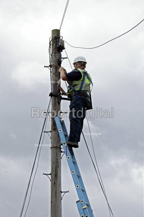 BT engineer up a telegraph pole repairing broken telephone cables that were damaged by high winds in Oxfordshire. - David Mansell - 2007-07-09