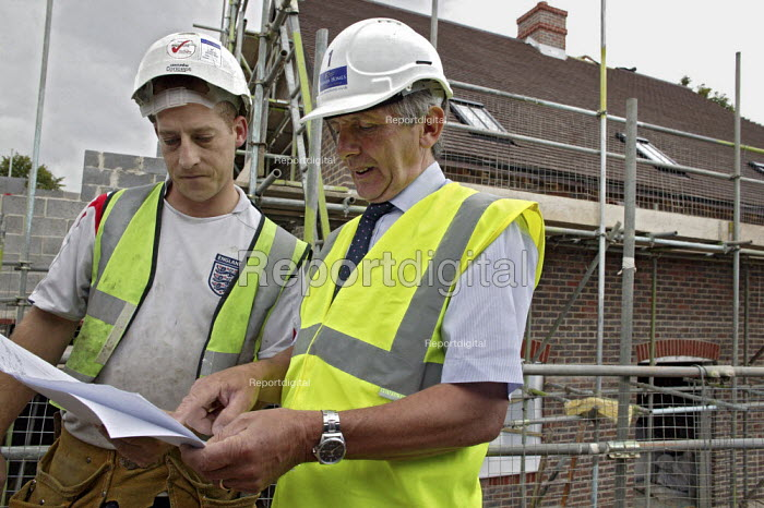 A site manager for the house building company Banner Homes talking with a subcontractor, while working on the construction of new homes in Chawton. - David Mansell - 2007-07-10