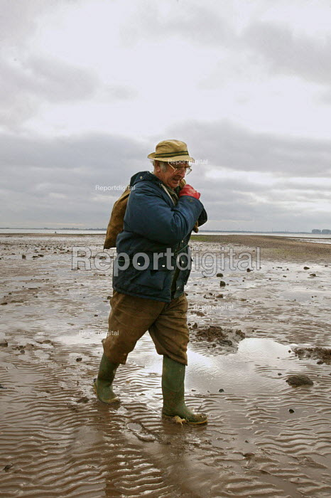 Local retired pensioner carrying a sack of young oysters so he can place them into controlled areas of the creeks. This allows the oysters time to grow larger ready for sale to the oyster bars and restaurants of West Mersea, Essex. - David Mansell - 2003-11-18