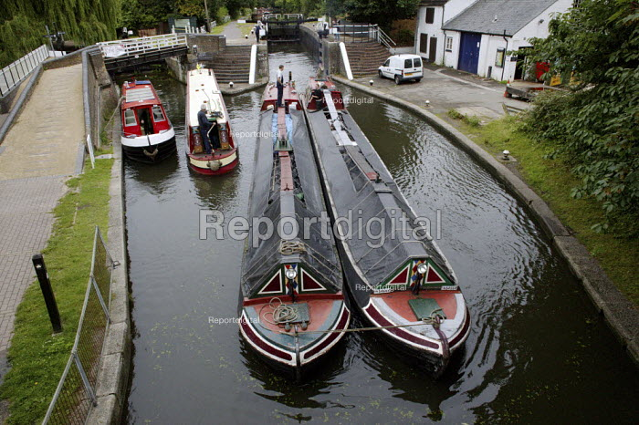 Two narrow boats tied together, to allow the boats to enter the lock gate system at the same time, on the British Waterways Grand Union Canal in Hertfordshire. The narrow boats are transporting commercial freight, carrying and delivering coal along the canal. - David Mansell - 2007-07-23