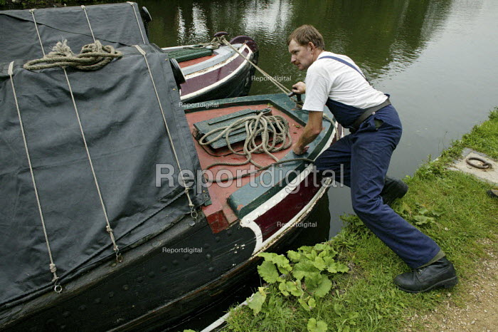 A boatman pushing two narrow boats tied together, to allow the boats to enter the lock gate system at the same time, on the British Waterways Grand Union Canal in Hertfordshire. The narrow boats are transporting commercial freight, carrying and delivering coal along the canal. - David Mansell - 2007-07-23