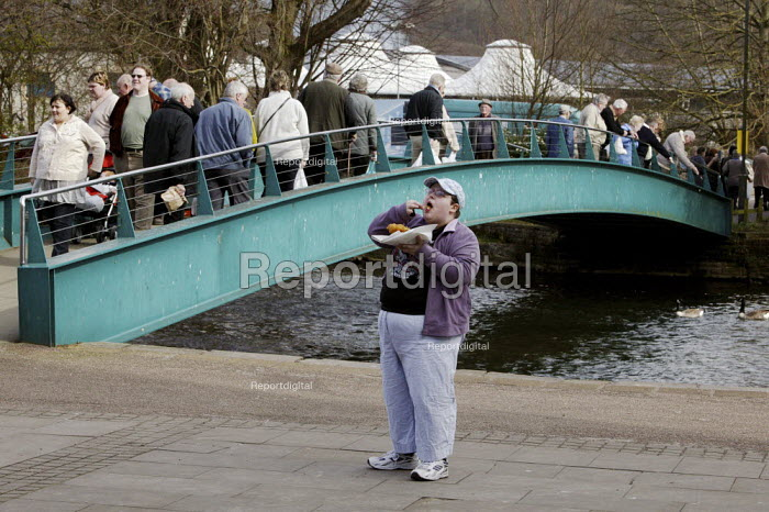 An over weight young woman eating her fish and chips as tourists cross a foot bridge while visiting Bakewell on market day, Derbyshire. - David Mansell - 2009-03-16