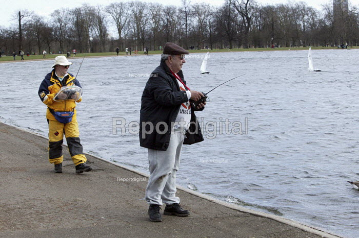Members operating their radio controlled yacht sailing boats while taking part in the Model Yacht Sailing Association, MYSA Round Pond Cup, at The Round Pound, Hyde Park, London. Ten Rater Class of model yachts - David Mansell - 2009-03-08