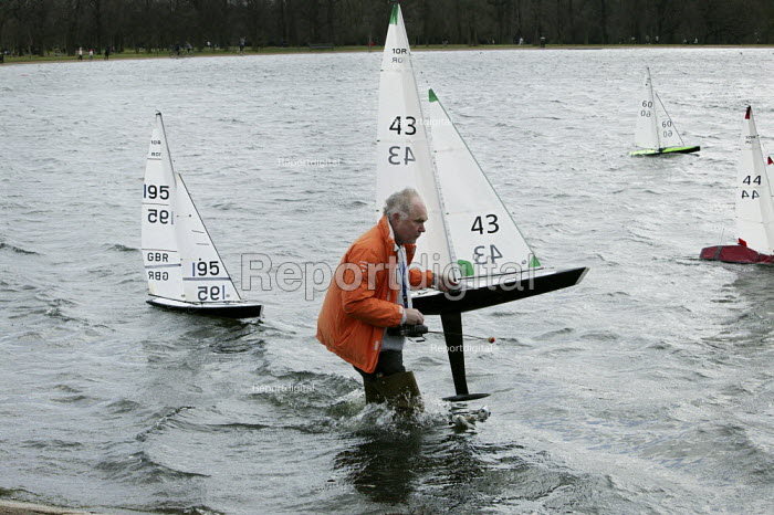A member removes his radio controlled sailing boat at the finish of the Model Yacht Sailing Association, MYSA Round Pond Cup, at The Round Pound, Hyde Park, London. Ten Rater Class of model yachts - David Mansell - 2009-03-08