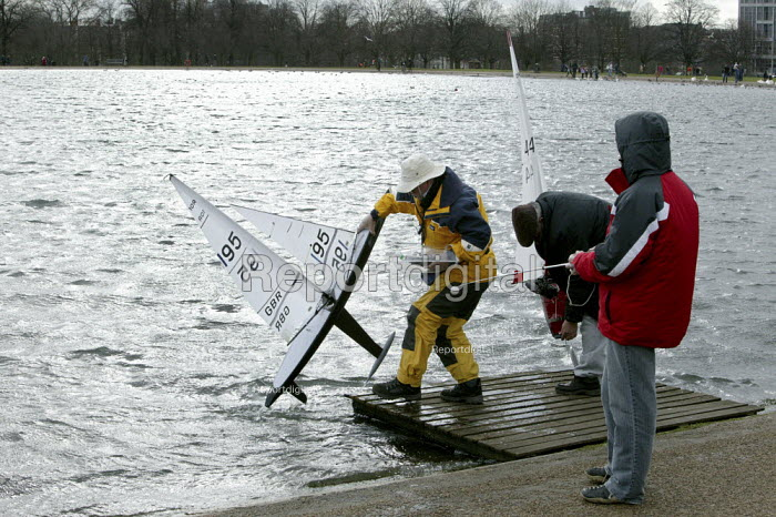 Members removing their radio controlled yacht sailing boats after taking part in the Model Yacht Sailing Association, MYSA Round Pond Cup, at The Round Pound, Hyde Park, London. Ten Rater Class of model yachts - David Mansell - 2009-03-08