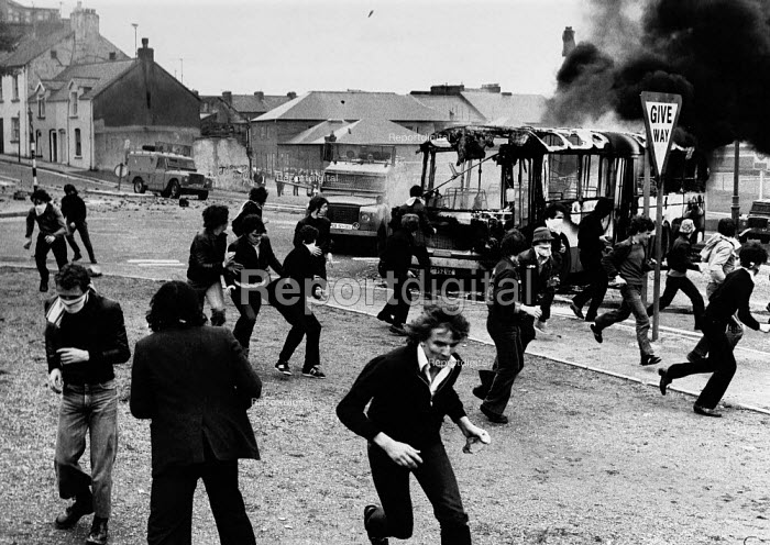 Rioting, The Bogside, Derry, Northern Ireland 1979, prior to the Annual Londonderry Apprentice Boys parade. A bus is highjacked and set on fire as rioting starts by a large group of catholic nationalist youths, who take to the streets at the Little Diamond junction in the Bogside of Derry after the unionists celebrated the Apprentice Boys parade on 12 August to commemorate the Protestant victory over the Catholics in the Siege of Derry in 1689. - David Mansell - 1979-08-11