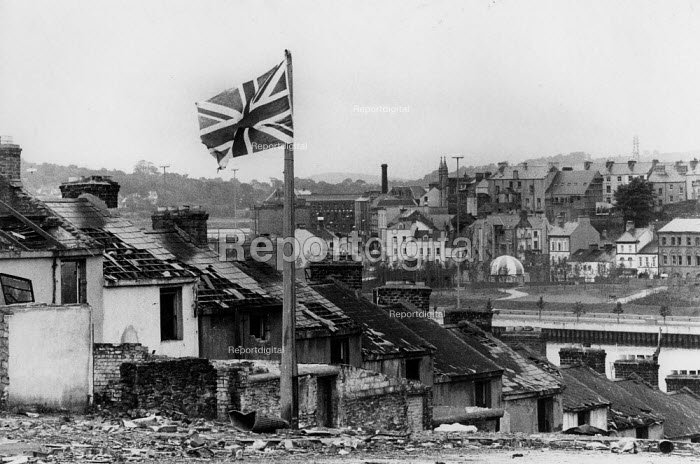 Union Jack Flag flying from a broken lamp post Derry 1979 amongst the ruins of a Protestant street of Victorian terrace houses, due to be demolished and the area redeveloped. Looking towards the River Foyle and the City of Derry. A wet Sunday morning after the Apprentice Boys parade - David Mansell - 1979-08-13