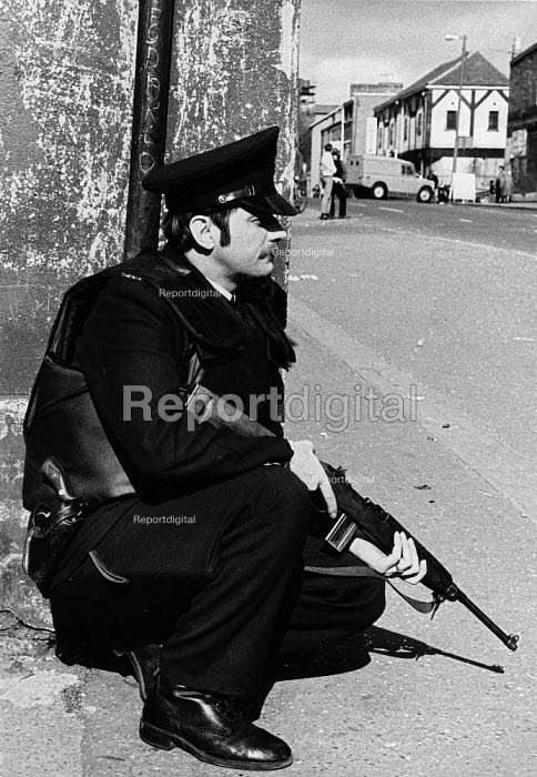 RUC policeman crouched down, gun ready, Falls Road, West Belfast, Northern Ireland 1979 - David Mansell - 1979-08-04