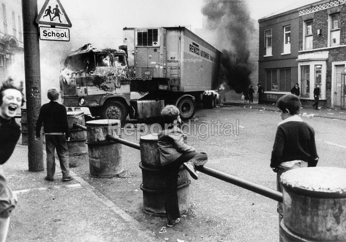 Rioting, Falls Road, West Belfast, Northern Ireland, 1979. Children and a burning HGV chip lorry blocking the road, prior to the Annual Londonderry Apprentice Boys parade - David Mansell - 1979-08-04