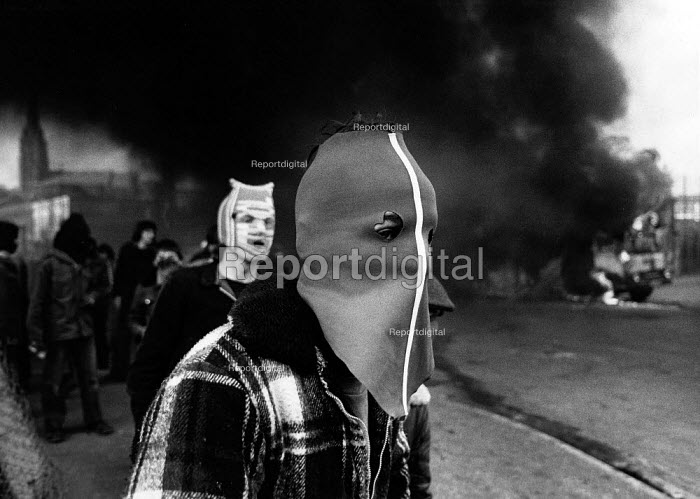 Rioting, The Bogside, Derry, Northern Ireland 1981 after the death of IRA prisoner Bobby Sands on hunger strike. Young rioters to protect their identity wearing masks made from tracksuit bottoms and a Liverpool football scarf, form part of a large group of rioters burning highjacked cars and lorries in the Bogside of Derry as part of the political unrest caused by the death of Bobby Sands. The IRA prisoner Bobby Sands started his hunger strike on 1st March and died 66 days later on the 5 May 1981. There were a total of ten hunger strikers who died in 1981. Their deaths resulted in serious rioting in the nationalist areas of Northern Ireland in particular the Bogside in Derry. - David Mansell - 1981-04-06