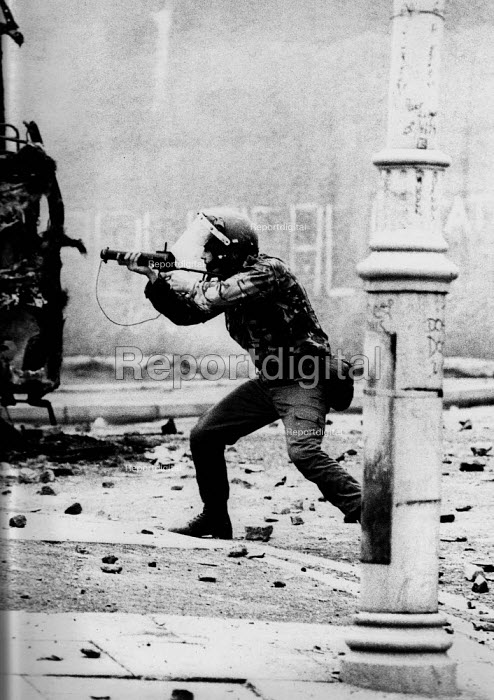 Rioting, The Bogside, Derry, Northern Ireland 1979 A soldier firing the baton rounds with a Swastika scratched on the side of his helme t- strongly associated with fascism and nazism. Rioting started in the Bogside of Derry after the unionists had celebrated the Apprentice Boys parade after which large groups of nationalist youths pelting the army with stones and molotov cocktails - David Mansell - 1979-08-04