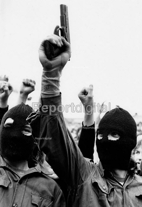 Hooded, armed IRA volunteer gunmen appear infront of the nationalist republican community, Andersontown, West Belfast, 1979 to celebrate the armed struggle for independence of the Dublin Easter Rising of 1916. The gunman is holding a 9mm Browning Automatic handgun. - David Mansell - 1979-04-12