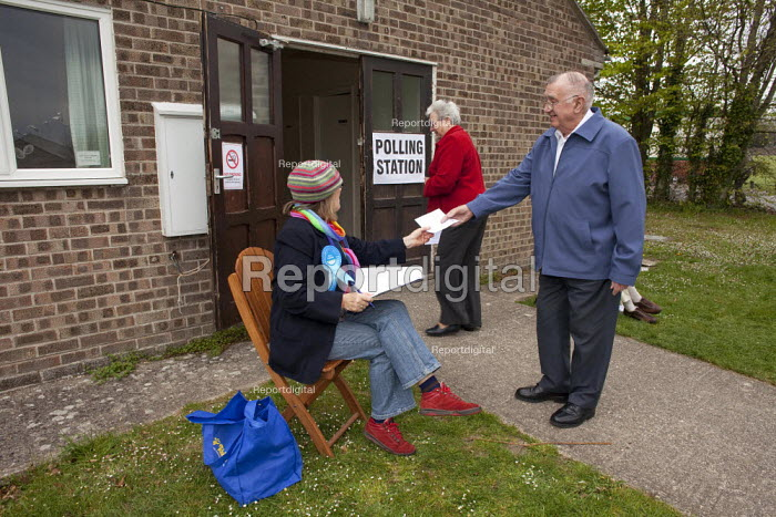 A political party polling station teller seen outside The Boy Scout and Girl Guide hut that was used as one of the Polling Stations in Dorchester in the Dorset West Constituency of the 2010 General Election. The teller's job is to ask for the voter's registration number so the local political party can try to work out how many people have voted in the constituency. A retired married couple seen entering the polling station to vote. - David Mansell - 2010-05-06