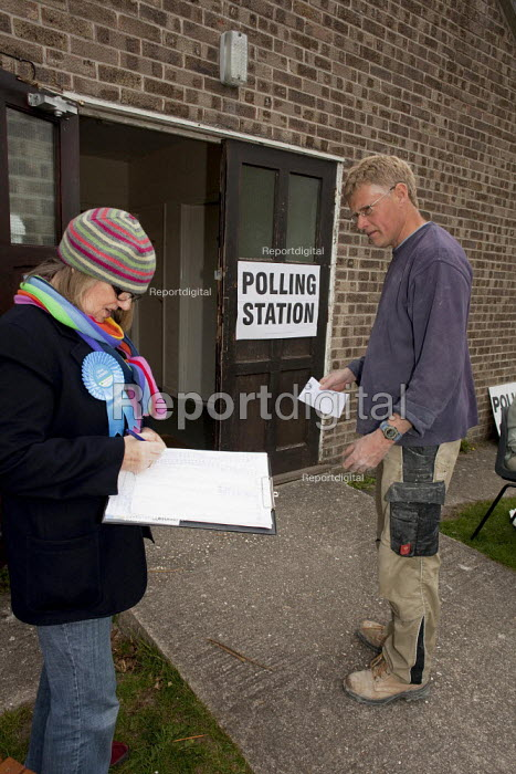 A political party polling station teller seen outside The Boy Scout and Girl Guide hut that was used as one of the Polling Stations in Dorchester in the Dorset West Constituency of the 2010 General Election. The teller's job is to ask for the voter's registration number so the local political party can try to work out how many people have voted in the constituency. A voter is giving this information before he enters the polling station to vote. - David Mansell - 2010-05-06