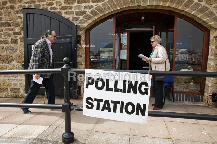 A retired male voter is greeted by a political party polling station teller seen outside The Salt House, West Bay Harbour, Bridport, that was used as one of the Polling Stations in the Dorset West Constituency of the 2010 General Election. The teller's job is to ask for the voter's registration number so the local political party can try to work out how many people have voted in the constituency. - David Mansell - 2010-05-06