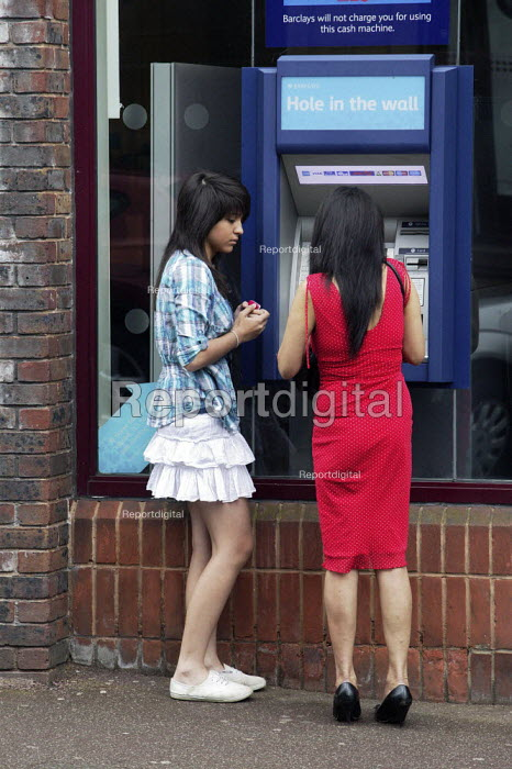 Mother and daughter using a Barclays Bank cash dispenser to withdraw cash in Chesterfield in Derbyshire. - David Mansell - 2009-06-13