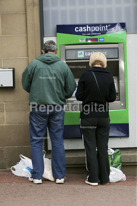A middle aged couple, a man and women customers using a Lloyds Bank cash dispenser to withdraw cash in Chesterfield in Derbyshire. - David Mansell - 2009-06-13