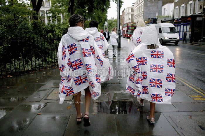 Young children walking down the Kings Road in Chelsea, London, dressed in white plastic Union Flag rain coats, after a very heavy downpour of a summer rain storm. - David Mansell - 2009-07-07