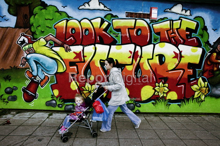 A young mother and child in a pushchair walk past a mural: Look to the Future (by LLOYD ROBERTS), on the shopping centre, the Gurnos council housing estate which dates from the 1950s, Merthyr Tydfil - David Mansell - 2010-11-08