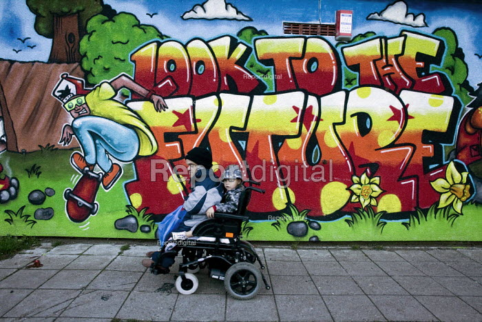 A disable man with a child going past a mural: Look to the Future (by LLOYD ROBERTS), on the shopping centre, on the Gurnos council housing estate which dates from the 1950s, Merthyr Tydfil - David Mansell - 2010-11-08