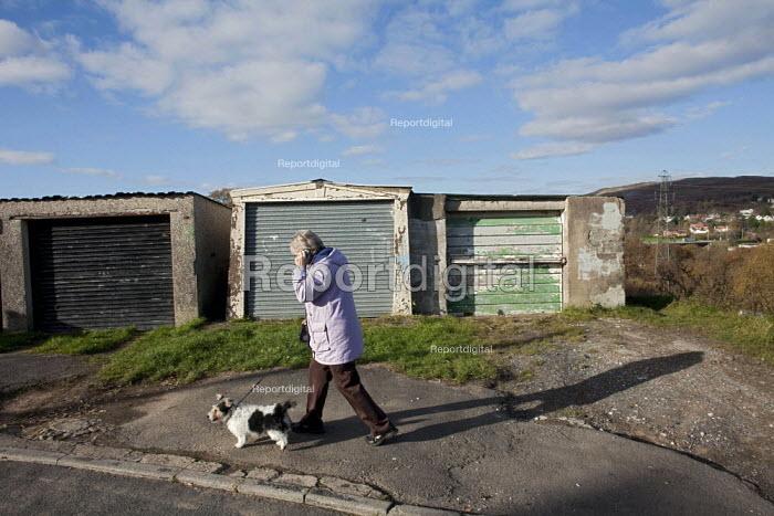 A retired pensioner using her mobile, as she walks her dog on the Twyncarmel Estate in Merthyr Tydfil. - David Mansell - 2010-11-10