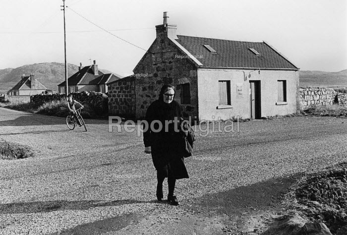 Woman in a traditional black dress crossing the road. Isle of Harris, Outer Hebrides, Scotland - David Mansell - 1977-07-10