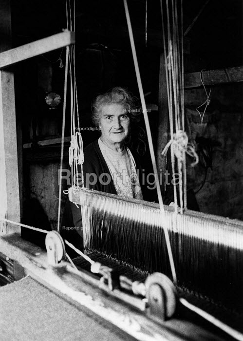 A Weaver at work weaving woll in a loom shed making Harris Tweed cloth, Isle of Harris, Outer Hebrides, Scotland. Harris Tweed is hand woven on a treadle loom at each weaver's home. - David Mansell - 1977-07-10