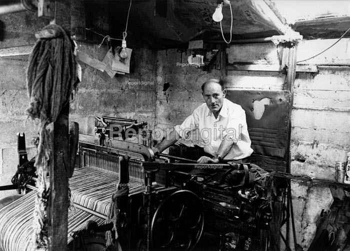 Weaver at work weaving woll in a loom shed making Harris Tweed cloth, Isle of Harris, Outer Hebrides, Scotland. Harris Tweed is hand woven on a treadle loom at each weaver's home. - David Mansell - 1977-07-10