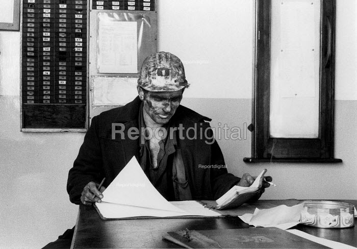 Manger wearing a pit helmet and miners lamp, looking at production figures for output. Snowdown Colliery, NCB, Kent April 1971 - David Mansell - 1971-04-10