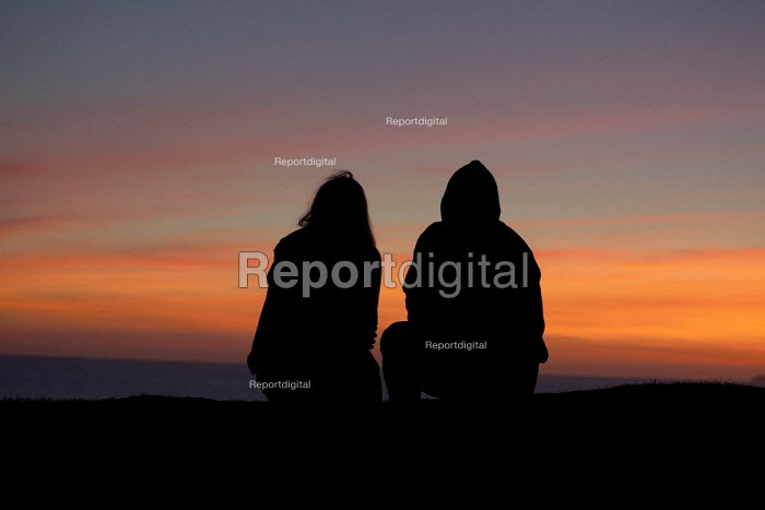 A young couple on holiday watching the sunset, Freshwater West, Pembrokeshire - David Mansell - 2012-09-05