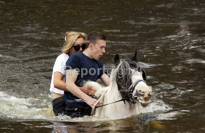 Appleby Horse Fair, Cumbria, washing horses in the River Eden. Young people often first meet their future marriage partners at Appleby Fair. Riding together are Arran Boot and Jasmine May, both 17 years old - David Mansell - 2015-06-07